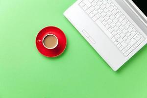 taza roja de café y cuaderno blanco foto