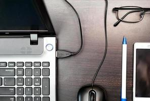 Laptop, glasses, cell and pen on wooden table backgrounds concept