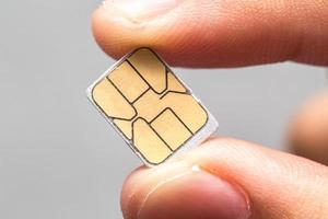 asimiento de la mano tarjeta micro nano sim aislada foto
