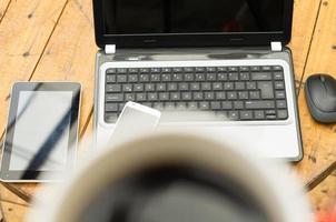 Taza de café borrosa cerca de la cámara y la computadora portátil con tableta foto