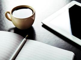 Tablet PC vacía y café, cuaderno con lápiz foto