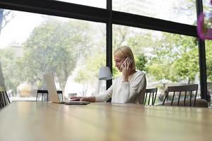 independiente trabajando en la distancia hablar en teléfono inteligente en café