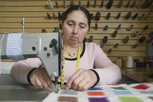 Mujer usando la máquina de coser en la lavandería foto