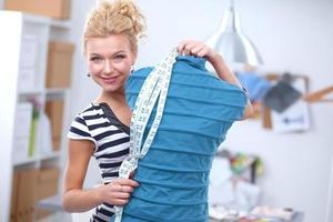 Diseñador de moda sonriente parado cerca del maniquí en la oficina foto