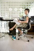 Young barefooted woman sitting in office, holding paperwork, smi