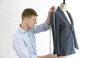 Tailor Measuring Suit On Mannequin In Studio