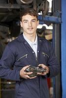 Retrato de aprendiz mecánico en taller de reparación de automóviles foto