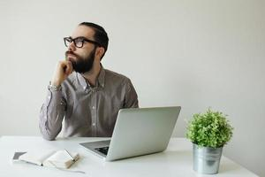 Busy man with beard in glasses thinking with laptop, smartphone