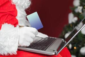 Santa buying by plastic card Christmas gift in Internet