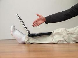 homem aperta a mão com o laptop.