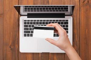 mano femenina sosteniendo un pago con tarjeta en una computadora portátil foto