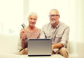 feliz pareja senior con laptop y tarjeta de crédito