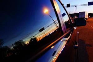 Reflection of a setting sun in Turku harbor in a car window