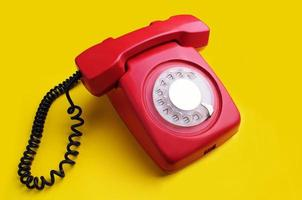 Red retro telephone on yellow background