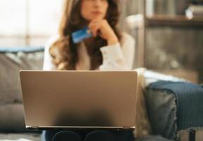 Primer plano de una mujer joven con tarjeta de crédito y portátil foto