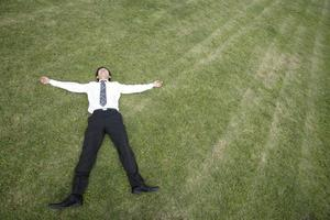 Businessman lying on lawn
