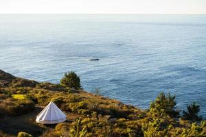 grande tente unique surplombant l'océan au lever du soleil
