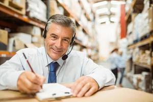 Smiling warehouse manager writing on clipboard photo