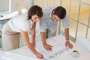 empresarios trabajando en planos en la oficina foto