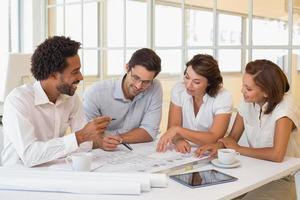 Grupo de jóvenes arquitectos trabajando en planos en una oficina foto