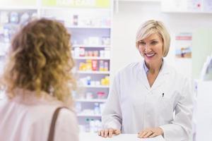 apotheker die bij klant glimlacht