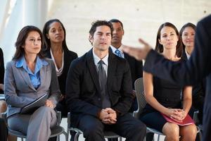 zakenlieden en vrouwen die aandachtig bij de presentatie zitten