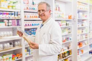 Smiling senior pharmacist holding envelope and prescription photo