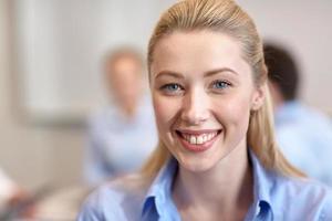 Gruppe lächelnder Geschäftsleute, die sich im Büro treffen