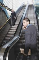 Business people on escalator business man using mobile phone