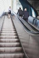 Business people on escalator business woman using mobile phone