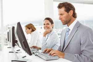 Business people using computers in office photo