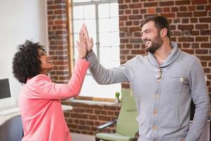 Business people high fiving at office