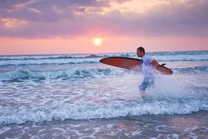 surfista corriendo en la costa en indonesia foto
