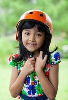 asiatische Kinder mit Helm im grünen Park