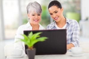 Senior madre e hija usando la computadora portátil