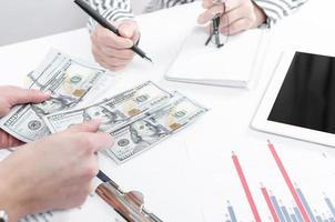 empresarios intercambiando billetes de dólar