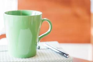 Closeup taza verde con bolígrafo y cuaderno foto