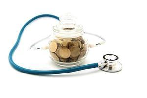 Estetoscopio con monedas en el ahorro, concepto financiero foto