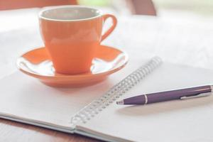 Coffee cup, pen and notebook on wooden table photo