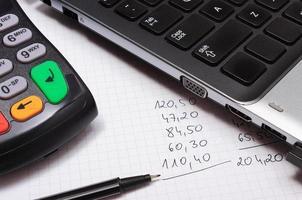 terminal de pago, computadora portátil y cálculos financieros foto
