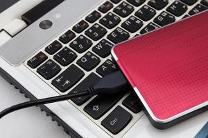 disco duro externo sobre el teclado del portátil, enfoque selectivo foto