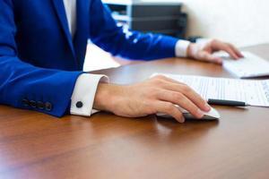 mano masculina que sostiene el ratón de la computadora con el teclado del ordenador portátil foto