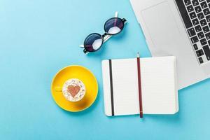 taza de café y laptop cerca de vasos foto