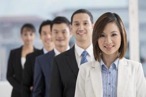 empresaria asiática liderando un equipo de negocios foto