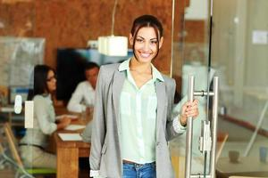 businesswoman standing in front of colleagues photo