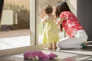 Cute mom and baby girl looking outside