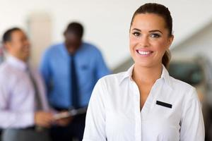 caucasian saleswoman standing at car dealership