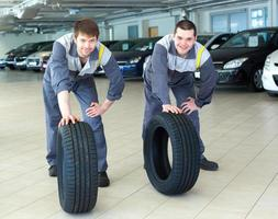 Two servicemen repairmen automobile mechanic with two tires photo