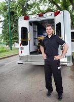 un emt parado cerca de una ambulancia foto