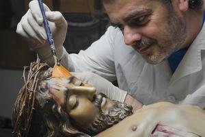 conservative restoring an image of Christ crucified on wood